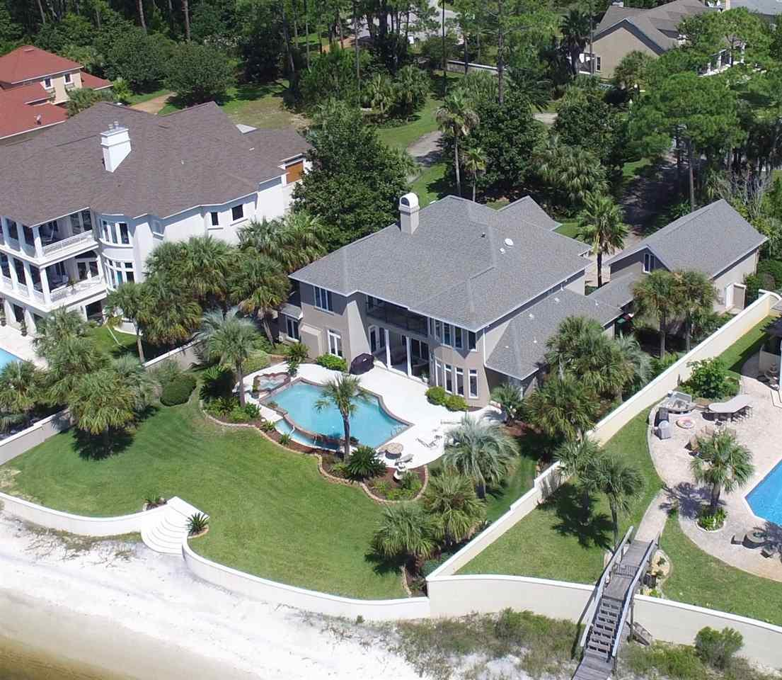 Spectacular Traditional 2-Story waterfront home with breathtaking views of Santa Rosa Sound and Navarre Beach. Home has beautiful pool with hot tub that can be seen with Sound views from 6 rooms in the house. The twenty foot high Foyer with custom artwork and leaded glass inlays are only surpassed by the elegant Oak Wood trimmed spiral staircase. Exquisite Custom Cabinets and Trim along with custom Travertine tile are featured exclusively on the first floor. The Library and Dining room have exclusively designed rare Coffered Ceilings. The Luxuriously elegant huge Master Bath will take your breath away! The enormous Master Bath has Travertine throughout with his and her double shower, Garden Jacuzzi Tub with indirect lighting, dual granite vanity plus spacious dressing area, large commode area with huge walk in closet.  The kitchen features Travertine tile with handmade European cabinets/granite tops with center island, GE Monogram Designer  appliances including 6 gas burner stove plus grill with High Capacity Hood, dual oven, dishwasher, built in microwave and Restaurant style size refrigerator! The Butler's gallery has stainless steel /glass wine cooler, separate ice maker and large overhead wine rack. The upstairs Media/Family room has balcony connected to two of the water front bedrooms for unbelievable views of the Inter Coastal Waterway and the swimming pool! Each of the waterfront bedrooms are connected to the other bedrooms via Jack and Jill full bathrooms. The upstairs hallway connecting all bedrooms and Media Room is all beautiful Oak Hardwood Flooring! The 3-Car Garage has upstairs build-out space for possible Mother in Law quarters or large workshop! The swimming pool/hot tub deck area are surrounded by lush landscaping and palm trees for your own private Paradise on the water. Take a few more steps away from the pool toward the water and you have your own private entrance to the white sandy beach on the Sound! A perfect luxury home for your Buyer!