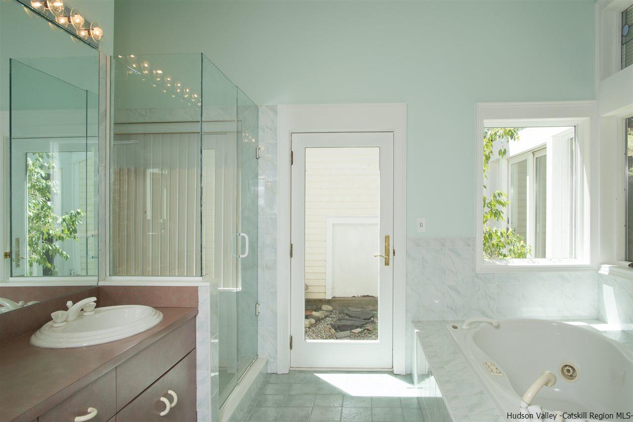 Master bathroom with frameless walk-in shower, whirlpool tub, dual sinks, views and access to atrium