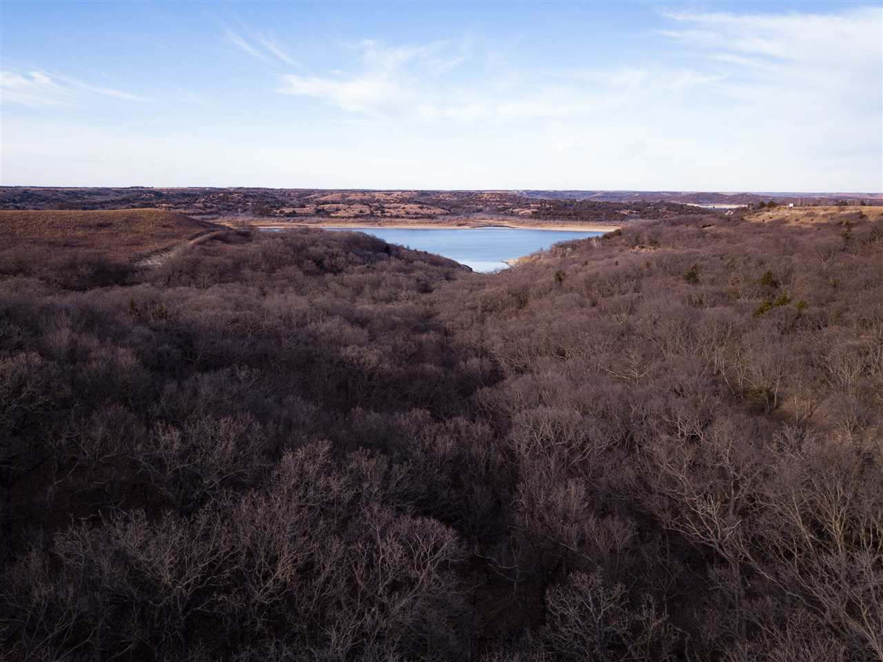Here is your chance to own breathtaking, scenic acreage close to Manhattan. Enjoy panoramic views of the Flint Hills and Tuttle Creek lake, all nestled within native pasture land and wooded hillsides. Perfect location for a custom build site and/or hunting/hiking getaways.   PLEASE BE SURE TO SHUT THE GATE BEHIND YOU AS THERE ARE HORSES ON THE PROPERTY!   *Be sure to click on the virtual tour link to view video of the property.*  Riley County may require a site plan to be approved to obtain a building permit.