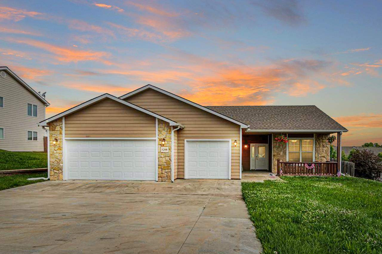 Enjoy the beautiful Kansas evenings right from your front porch of this, like new, zero step entry 3 bed, 2 bath, triple car garage home. Located on the highly favored Manhattan west-side and a very short commute to Ft. Riley, KSU, shopping & restaurants makes this home very desirable. School attendance for this home is Woodrow Wilson Elementary and Susan B. Anthony Middle School.  The kitchen is gorgeous with its custom cabinetry, granite counter tops, stainless steel appliances, a counter bar and is open to the large dining area, and is overseeing the Livingroom area. All bedrooms of this one level home are very well sized. One will find an oversized en suite as well as a spacious walk-in closet adjacent to the main bedroom which easily fits a king sized bed. The privacy fenced in yard offers a deck for all your entertaining or relaxing needs. Call/text Sabine Butler with NextHome Unlimited at 785-307-0703 to schedule a showing.