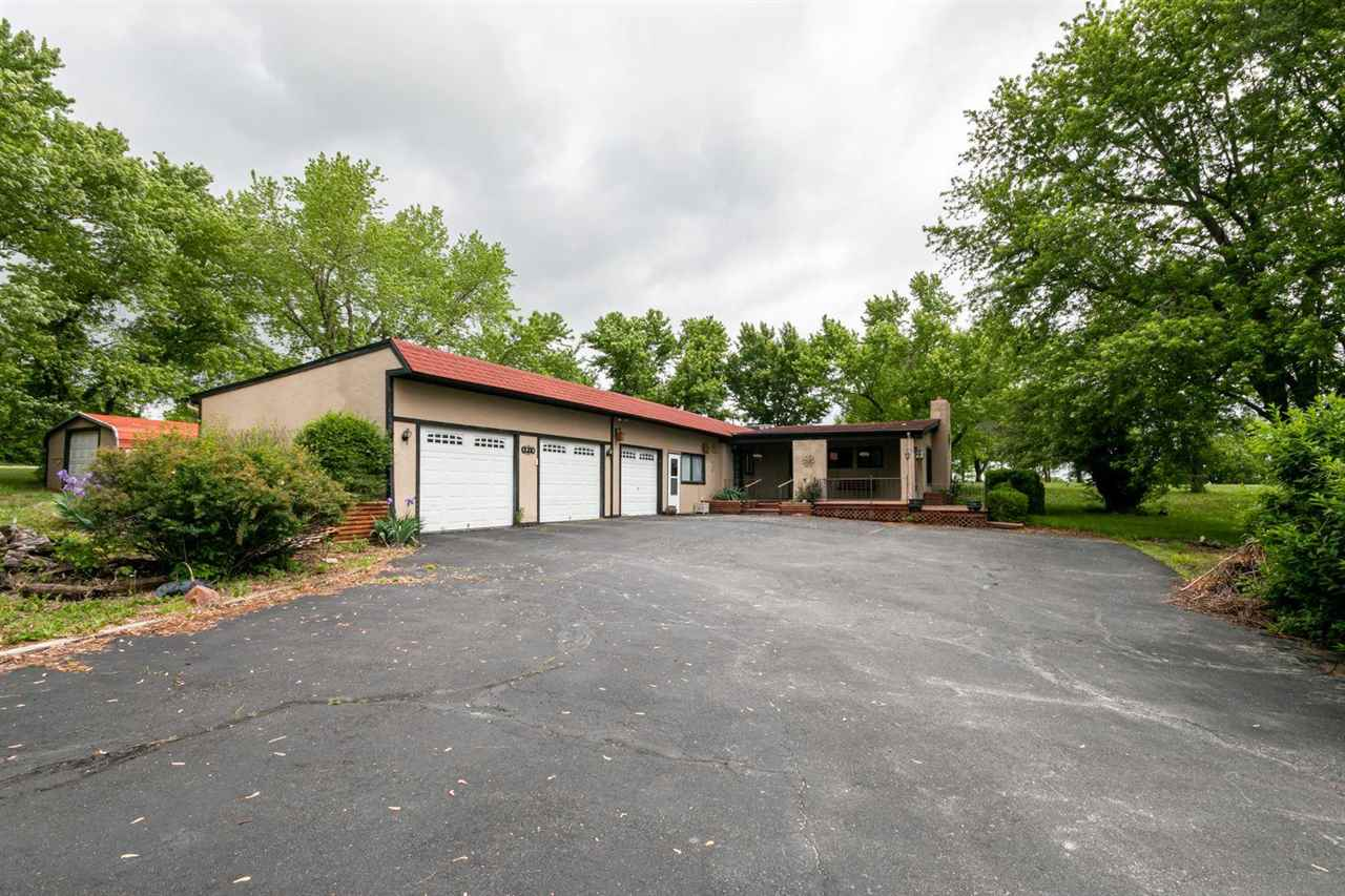 """Spanish Style Home that sits on 2 acres.  Wood burning stove that sits in your large living area.  Nice size kitchen with Corian Countertops and lots of counter space. Master bed is located on main level and second conforming room could be converted back into a bedroom or left as an office space.  3 car garage, screened in porch which allows you to enjoy the scenery.  House will be sold """"as is"""".  Contact Peggy @ 785-706-3303 for more information."""