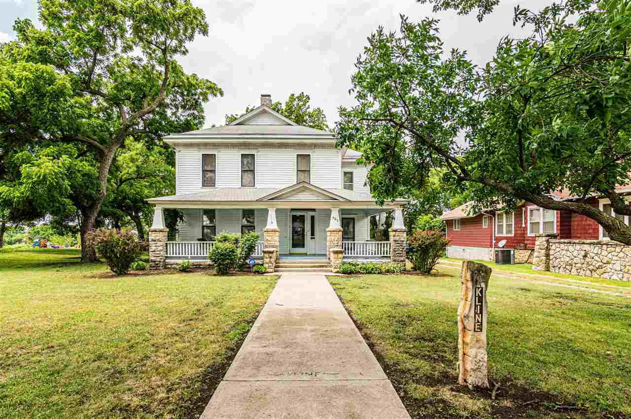 Built in 1887, this prestigious 2 story home sits on close to ½ acre. A wrap-around front porch gives you access to a second entrance. Stately & historic, the house has original woodwork, multiple stained glass windows, a foyer w/open staircase & original hardwood floors throughout. Original glass pane pocket doors separate the music room w/fireplace from the liv. room. The spacious formal dining room could hold seating for a large party. Lots of storage is located in the kitchen w/original cupboards. All appliances stay. ½ bath on the main floor.  An addition of a main floor laundry & family room.  Enjoy the deck off the family room. Upstairs is a wonderful master bedroom w/sitting area (a double room), ¾ bath & 2 additional bedrooms. A gazebo highlights the back yard, along with the 2-car oversized garage w/workshop. The yard has blooming flowers, landscaped areas, a waterfall, garden space & a nice tool shed. Contact Becky Schwab, NextHome Unlimited, 785.479.1920 for info.