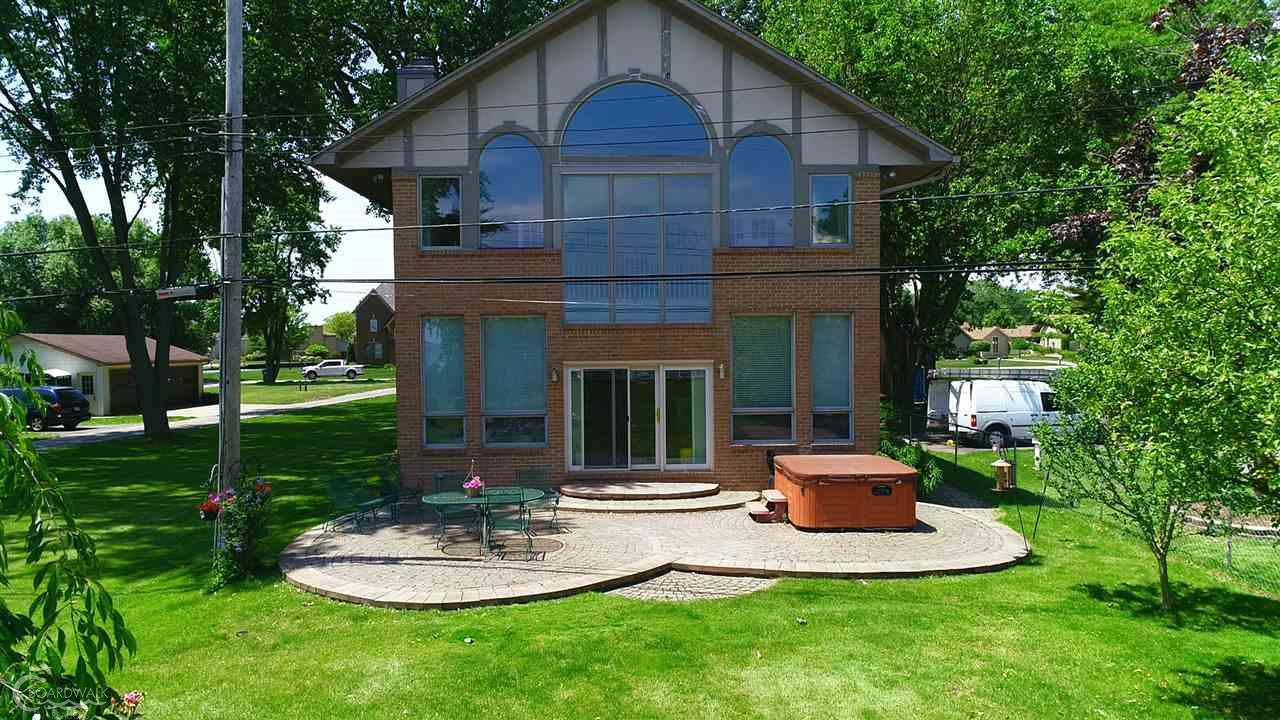 Extraordinary custom built home on beautiful Lake St. Clair! 4 ton boat hoist, 2 jet ski lifts, new tie backs on seawall, floating dock, paver patio, hot tub & stone fountain! Great room w/wall to wall windows (wallside), fireplace,custom blinds,cornice boards & built in padded benches! French beveled doors leads to den w/fireplace & built in bookshelves. Nice size office on main floor. Spacious kitchen w/Corian counters,hardwood floors,butler sink & tons of cabinetry! Master is amazing, w/fireplace, walk in closet and ceramic bath. Jetted tub in master&main floor bath. Master & 2nd bedroom lead to Bridge that over looks the water! 2 seating areas up stairs to watch boats go by! Attached garage heated and cooled. 4 car detached garage w/drain, loft & garage door openers. New roof 2017, new sump, new furnace 2 zones & air. Whole house generator! New dishwasher!