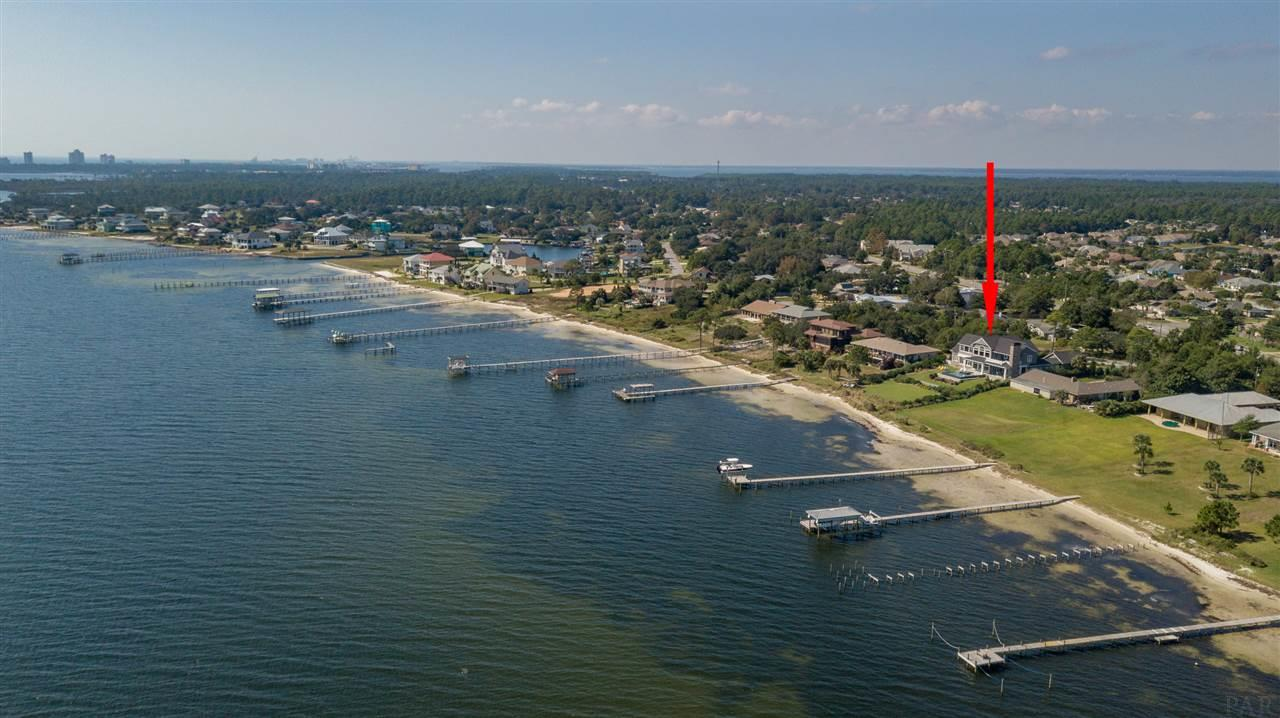 """Graceful waterfront home on Big Lagoon invites you to enjoy its spectacular, unobstructed, water views toward Johnson's Beach and the Gulf of Mexico beyond. Built in 2016, this elegant home has all the charm of a New England coastal paradise, with water views from nearly every room.  Peace, serenity, and natural light abound in this airy open floor plan. Enter the formal foyer and walk into the expanse of the great room and dining area that have floor to ceiling windows that welcome the water view into this home. Entertain your friends in the open chef's kitchen that has an extra large pantry with rolling ladder for those higher shelves and Dumb Waiter to the Second Floor perfect for entertaining on either level. Submerge yourself in your infinity edge pool, then sit and watch the sunset from your covered back porch with outdoor kitchen and magnificent rock fireplace.  Master-suite is on main level, with elegant soaking tub, separate shower, water closet and large dressing room.  The second floor has a huge wood paneled gathering room, with dumb-waiter, and a second large covered porch with rock fireplace. 2 additional bedrooms share a Jack-n-Jill bathroom with 2 separate dressing areas.  The wood paneled study can be used as a 4th Bedroom.  This is a home where you can relax, watch dolphin play, boats pass in the distance, and pelicans coast to their sanctuary at nearby Big Lagoon State Park. Only 7-10 minutes by boat to the Gulf of Mexico! Just a few minutes drive to Perdido Key, Gulf Islands National Seashore, Restaurants, Golf Courses and our famous white sand beaches. Please look at the 3D Virtual Tour to give you a sense of living in this magnificent home.  It is an amazing home and floor plan! Located in FEMA zone """"X"""" for lower cost insurance!"""