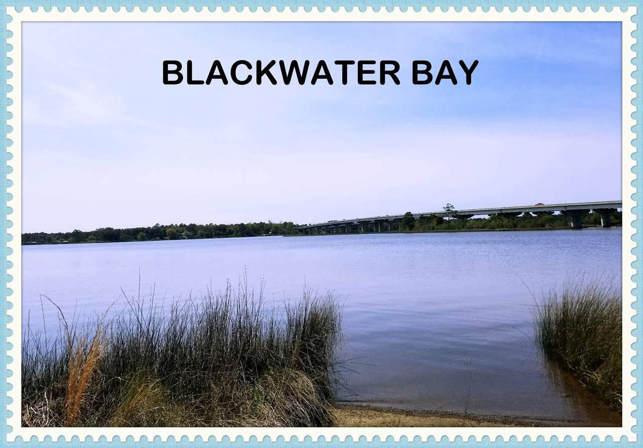 "This Extraordinary ""Estate Sized Property"" is totally cleared, groomed and well kept! 4.85 Acres with 270ft of Blackwater Bayfront Property at a depth Road to Bay of approx. 1000ft. I-10/Ward Basin Rd less than 5 minutes away! A Private concrete boat ramp at waters edge, and a barrier of Local Shoreline Marsh Grasses provide the perfect natural habitat for our local fishery with an added plus of providing shoreline stabilization. This impressive waterfront location is zoned R-1 Single Family Residential. A previous home that was destroyed in Hurricane Ivan 2004 was removed, but leaves utilities like Water, Cable, and Electric at the properties edge. Note 30amp electric pole in place for the buyers weekend RV trip while building! Also new to this area is Sewer availability, Tap Fee Due! Note there is a discount available with the demolition of existing septic tank. An Old tennis court can be updated if tennis is your game, used for parking or a recreation area; or you can remove it. An awesome Western Sunset View added to a light show from the I-10 bridge at night gives you something watch with your significant other than TV! Another added plus are the remnants of an old dock which should reduce permitting time and requirements to rebuild. Please do not enter property without calling for permission, and DO NOT DRIVE ONTO PROPERTY at anytime! Your choice of fishing, Inshore Back Country, Bay, Redfish, Specs, and Flounder, go crabbing or head upstream for Fresh Water Species; or even take a short jaunt to Yellow River South! This entire area is considered a Pristine Waterway with various conservation areas nearby to protect the Natural Environment. This parcel just needs the right buyers that want to build their own Private Estate on the Waterfront! UNIQUE AND PRICED TO SELL!"