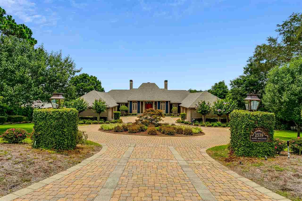"""STATELY WATERFRONT HOME WITH EXPANSIVE VIEWS OF BAYOU TEXAR....  Situated on 3/4 of an acre with 150' of water-frontage, you'll find this immaculate custom built home with 10,000 sf under roof. You're welcomed to the property by two gas lanterns street-side and a paved driveway with ample parking for guests. The Gallery style foyer features two alcoves that can house sculptures in addition to wall art. The expansive Living Room features 14ft ceilings, wainscot paneling and a gas fireplace. The 3 sets of mahogany doors open to the spacious veranda appointed with Sunbrella fabric outdoor panels that can retract to give you as much and as little privacy as desired. The Kitchen features custom built mahogany cabinetry with substantial hardware pulls, stainless steel appliances which include a gas range, double ovens, Sub-Zero full size fridge and freezer, and ice maker. Open to the Kitchen is the family room which makes for a great gathering space. Thru the family room you'll  find the refined formal dining area with floor to ceiling windows that will accommodate a large dining room table for all the family gatherings. On the opposite side of the home you'll then encounter the office with distressed custom cypress cabinetry. Past the office you'll enter the Large Master Suite which overlooks the water, an elegant bathroom with double vanities, jetted soaking tub and a spacious closet with two separate areas for him and her. Once downstairs you'll be greeted by the large family area which acts as the center for the two guest ensuite bedrooms. Downstairs you'll also find a large home gym which houses a dry sauna, and also a large workshop with garage door. Once in the backyard you'll be mesmerized by the landscaping, water-views, and large gunite lap pool. Last but not least, this is a boaters paradise.  The dock was refinished in 2018 with storm resistant """"Thru-Flow"""" decking.  The expansive dock also features two boat lifts, wave runner lift, and uncovered boat slip."""