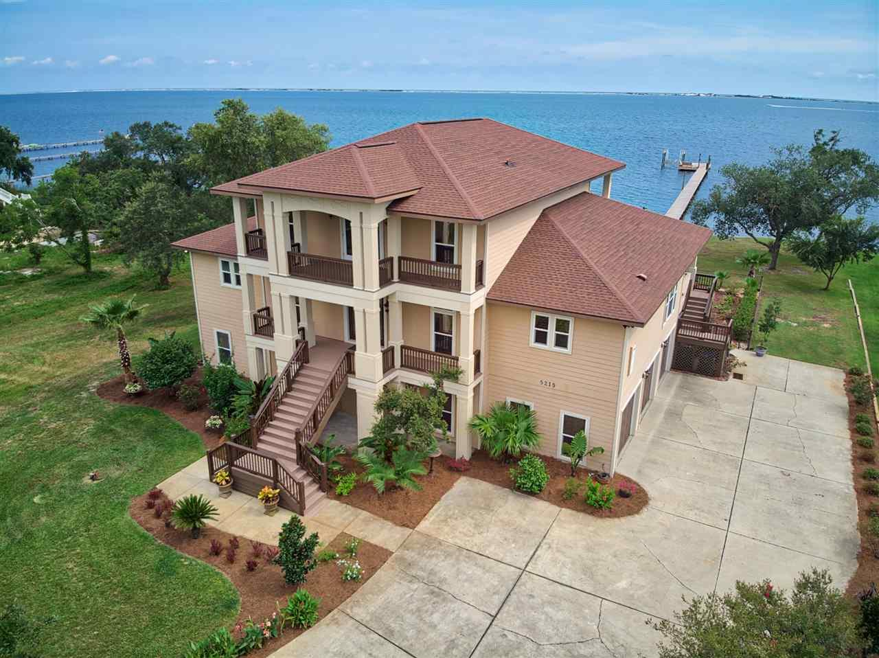 Welcome to paradise! This stunning custom built waterfront home is an entertainer's and boater's dream. The professional landscaping, gunite pool, beautiful stained front doors & large .69 acre lot gives this home impressive curb appeal. New rails and stairs throughout the exterior with fresh paint. The open floor plan is ideal for entertaining and encompasses a spacious dining & kitchen and living areas. Water views from almost every room in the house with 10' ceilings throughout. The kitchen is stunning with granite countertops, custom cabinets, 6 burner gas stove, endless cabinets/storage, pot filler, filtered instant hot & cold water, Italian travertine backsplash, wine/drink fridge and ice maker. The spacious pantry off the kitchen has another fridge & more cabinet space. Beautiful built in shelving in the living room with a two sided gas fireplace. Wake up in the oversized master bedroom to a sunrise over the water every morning. Master bath has a jacuzzi tub, separate travertine walk in shower, double vanity, granite countertops and a large walk-in closet with wood shelving and is wired for a center island. Laundry is off of the master closet for convenience. 3 large bedrooms upstairs with 2 full baths plus extra living space for an office, reading area or workout space. 2 spacious walk in closets upstairs as well. Home has 2 closets that can be converted into an elevator. On the bottom floor, off of the pool deck is a 800 sqft cooled living space and a full bath. This room is wired for a projector, perfect for kids hangout space!! There is also an outdoor kitchen making the 14ft wide porches perfect for outdoor living & dining. Watch the annual cigar boat races, blue angel shows & sailboat regatta from your back deck!! New dock in 2018 with 10,000lb boat lift & green fishing lights at the end. Home has 3 HVACs, 2 tankless hot water heaters, 3 car garage, surround sound & plantation shutters. Don't miss your chance to live in this dream home!