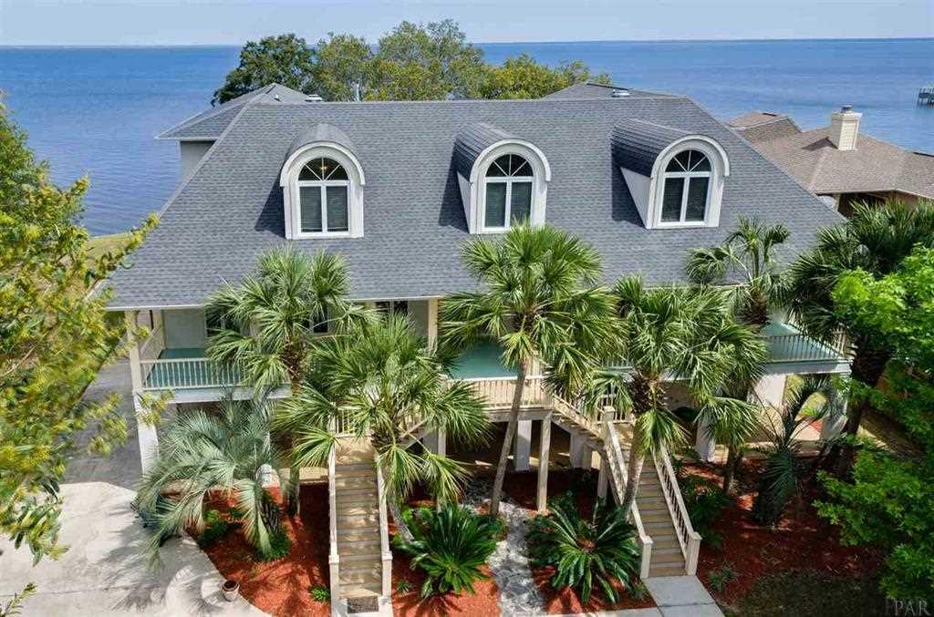 One of a kind waterfront executive estate! This expansive three story home features a screened pool, a boat dock and offers water views from almost every room! The picturesque setting highlights over one acre with beautiful oaks and palm trees. It also has multiple outdoor living areas and covered wrap around balconies to enjoy the sunsets. There are 5 bedrooms and 7 full baths with beautiful hardwood floors throughout. The design featuring separate kitchen/living areas is perfect for a multi generational situation or large family. On the first floor there is a fully equipped kitchen, recreation room, air conditioned workshop, and a waterfront living room with a fireplace. The second floor is the main living area with an open kitchen, breakfast nook, formal dining room, living room, piano room, study with wet bar, guest room with guest bathroom, and a second master suite with large bathroom. The third floor has two other guest rooms with private baths, an additional sitting area, and the master suite. The spacious master suite has a beautiful waterfront sitting area, large bathroom with 2 walk in closets, a tub, and a separate shower. Everyday is truly a vacation with the screened swimming pool and a dock equipped with a boat lift and observation deck.