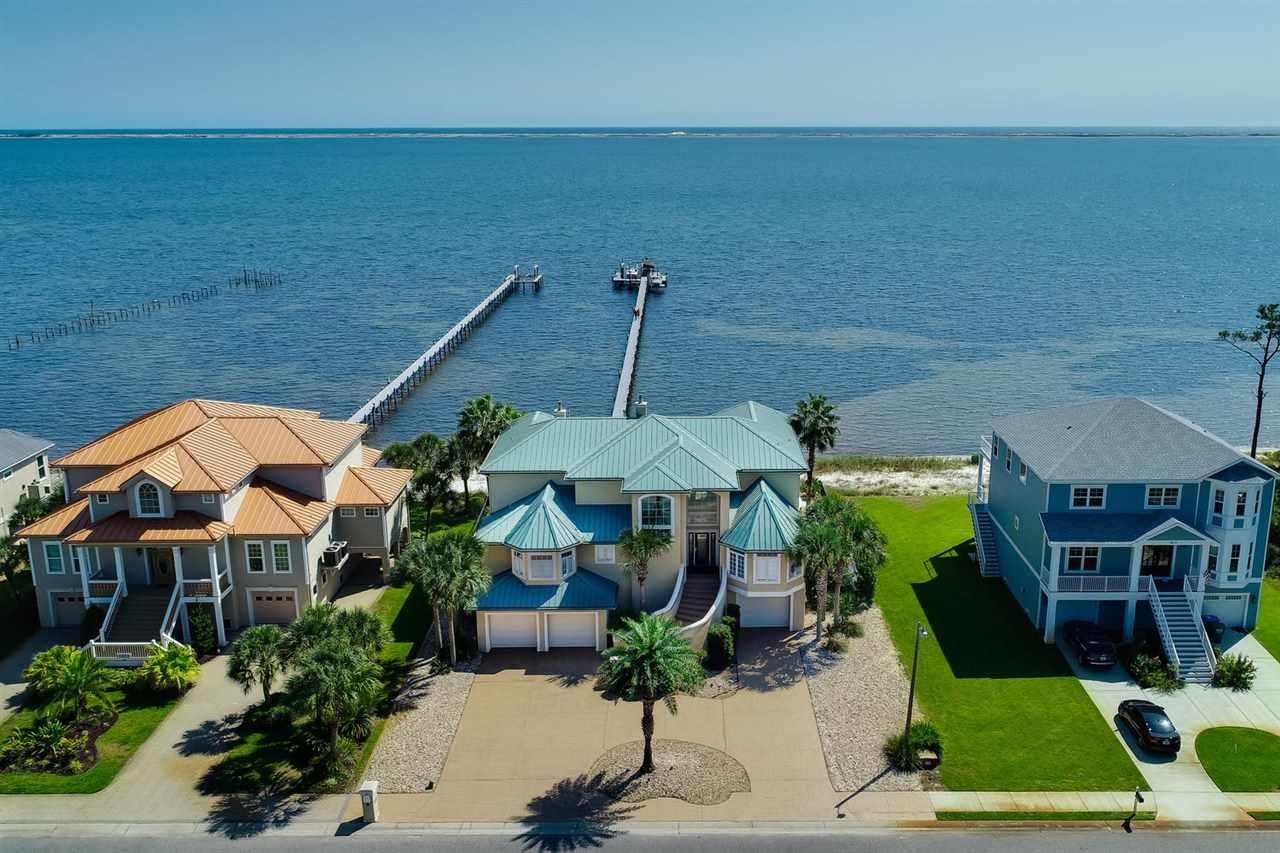 This absolutely stunning 4br/5ba waterfront home in Gulf Breeze has more upgrades and amenities than you can imagine. You'll find views of the Santa Rosa Sound from almost every room, and if that isn't enough, you can walk out of the back door and straight to your own 90ft beachfront. Enjoy the freshly painted interior, an elevator, a man cave with billiard table, 6 bay garage with new doors, high gloss floors, and lighting, new appliances in the indoor and outdoor kitchen, a fully functional home gym, a whole-house vacuum system, and new carpet throughout the entire home. Head outside and find fresh paint on the exterior, a heated pool with new liner, pool bar with remote retractable awning, 8 person hot tub and spa, and a 300' dock with Tiki bar and two recently refurbished boat lifts.