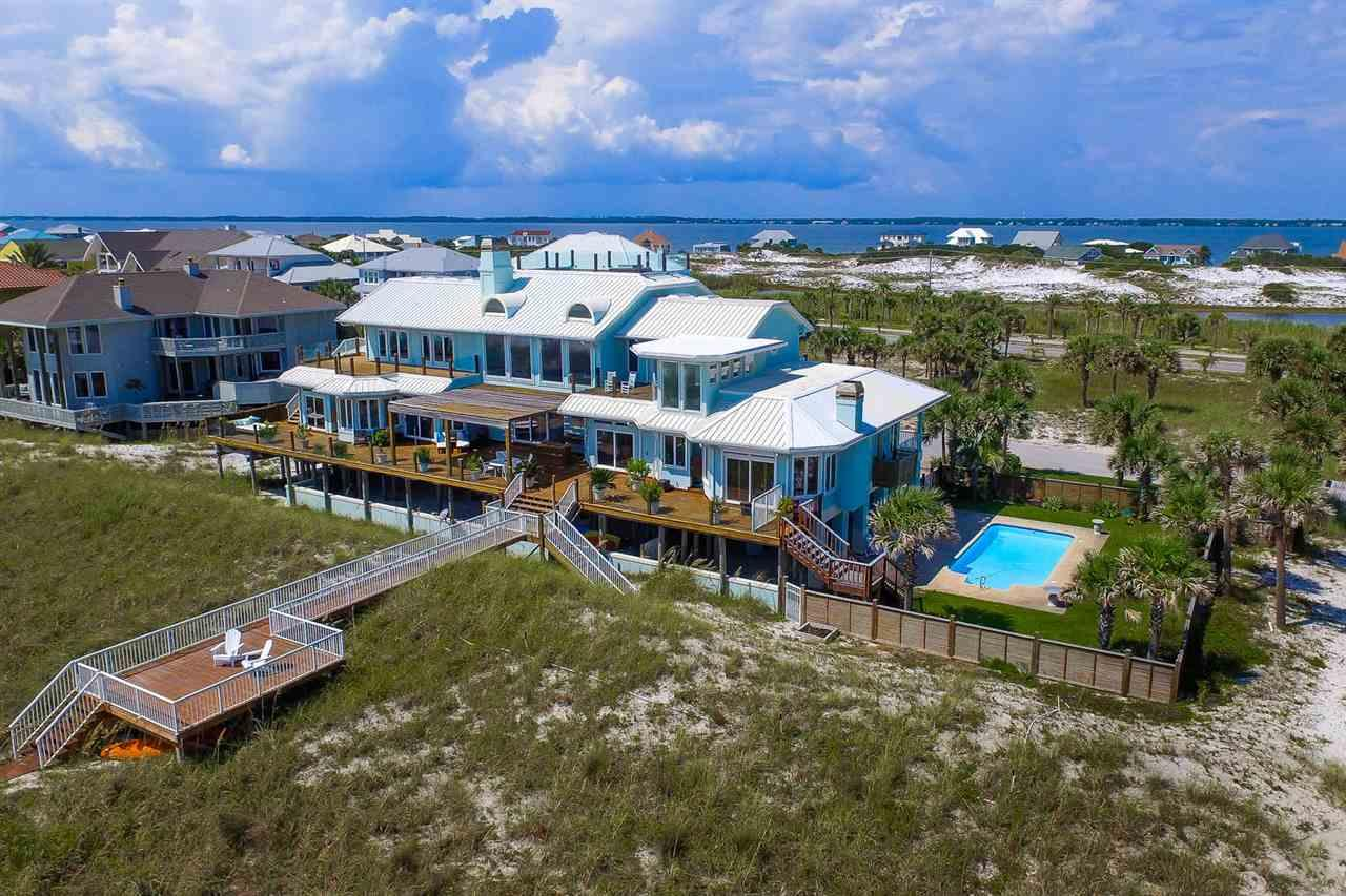Rare find! 200 feet of water frontage on the beautiful Gulf of Mexico! This 7600 square foot home offers breathtaking views from many rooms and the abundance of deck space. There is a private walkway to the sandy white beaches and emerald green waters of Pensacola Beach. The property includes a gulf front pool along with two inland lots across the street. This land would be perfect for a tennis court or basketball court. Open the front door and experience a true wow factor! Discover two story ceilings with stacked windows that offer incredible views. The 7600 square feet of living space boasts a separate guest apartment. The apartment features a private entrance, a separate living room and bedroom along with a mini kitchen.  With seven bedrooms, eight bathrooms and two half baths, you will have more than ample space for family and friends! The kitchen is perfect for entertaining large crowds. It has a gas cooktop with separate griddle, double ovens, a warming drawer, two dishwasher drawers and a full-sized dishwasher. Off the kitchen is the spacious dining room overlooking the water. After dinner, serve sunset drinks from the bar featuring a wine cooler and drink cooler. Enjoy the gulf breezes from the abundance of decks on the main floor or upper level. The master suite is on the main level. This retreat features a gas fireplace along with his and her baths. There is a crow's nest on the roof level with about six hundred feet of deck space. The view is amazing! This would be the perfect spot for watching the Blue Angels, sun bathing or reading a book! The garage offers plenty of space for vehicles, kayaks, surf boards, and fishing gear. This is truly a rare find . . . an expansive home offering two hundred feet of gulf frontage, a pool, and two interior lots!