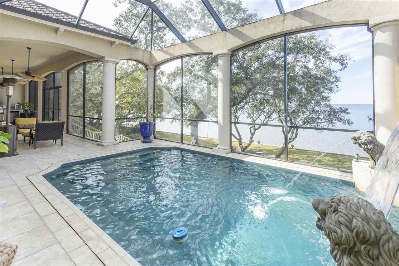 Waterfront East bay ICF home with privacy, elevator, home theatre, 5,000 sf of  storage space, pool & quiet area on culdesac in Navarre.  Privacy galore in this culdesac location near the Hidden Creek Golf Club. Ten minutes from Navarre Beach.   This bay home is nestled among the ancient oaks and positioned perfectly for beautiful sunset views.  The elevated pool has a spillover waterfall for added ambience adjacent the living and master bedroom area.  Master suite has a huge separate bath with over sized shower and his and her closets,  Home movie theatre, executive library/office with built in shelves and gas cooking. Large formal dining room and artist studio. Library has lovely appointed shelving and lighting and wood floors.  Beautiful kitchen with cherry cabinets, large center island, granite and stainless steel appliances. Impact windows, metal roof,  and custom features throughout.  Wet bar is conveniently across from the theatre. Down stairs you will find storage space available, which is close to 5,000 sf of space. Close to Navarre Beach, this home is not part of a HOA, so no rules or restrictions. Bring the RV, 2 pads, water, sewage, 50 amp plug. The entire first garage level has over 1,000 sf of storage additional to garage. Yard was professionally landscaped with abundant seasonal flowering shrubs.