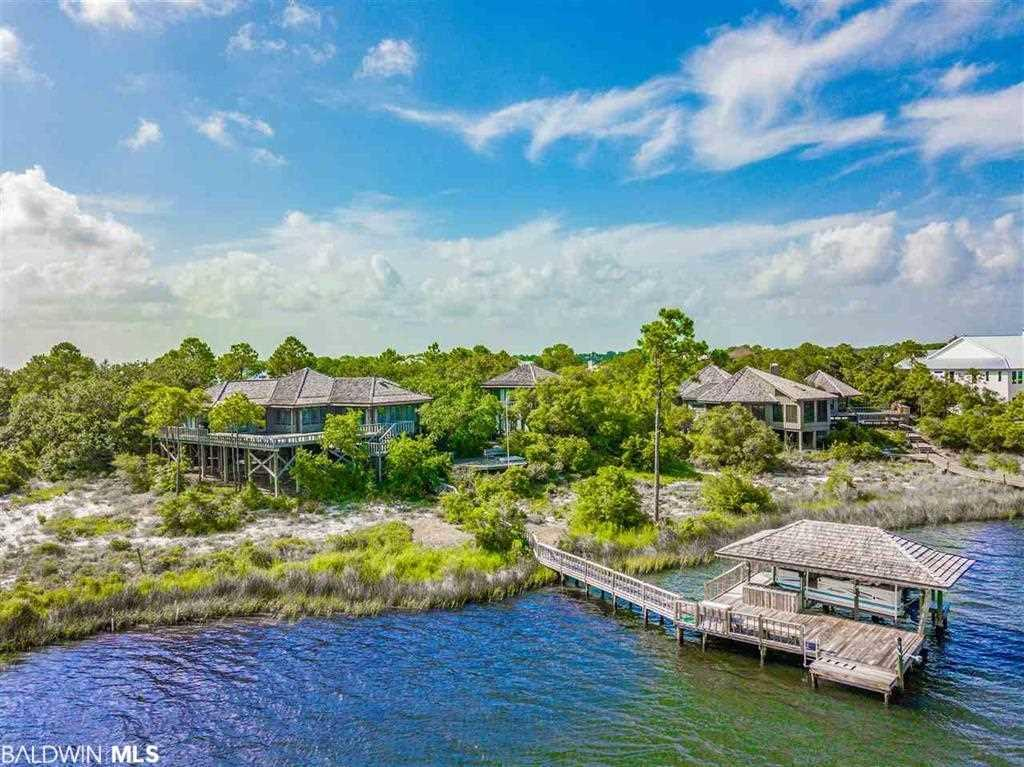 3 OLD RIVER LOTS !!!! A rare opportunity to own a ROMANTIC beach home with more than 300' OF  WATERFRONT on EXCLUSIVE Ono Island. Featuring panoramic views overlooking Old River and Rabbit Island, this architectural gem is nestled on three beautifully wooded lots with high elevation. The main house features an open floor plan for entertaining along with a kitchen, sitting room, den, dining area, and two spacious bedrooms with en-suite bathrooms. The central room opens out onto a broad front deck cantilevered over a 15' sand dune providing sweeping views of the water and a pristine state park on the far shore. A stand-alone guest house is two-storied with studio living on each level including large private bathrooms and balconies. The main house and guest house are connected by wooden walkways surrounded by garden areas. Between the two homes is the SWEET SPOT – an oak-shaded rendezvous point with a heated whirlpool spa and lounging bench for optimal waterfront relaxation under the stars. Follow the wooden pathway down to a spacious dock featuring a large, covered boat slip, bench, running fresh water, and open deck – a perfect place to swim, fish, or make a quick jump over to Rabbit Island in your kayak or Jon boat. The house is available unfurnished or furnished with select items from New Orleans antique dealers and other sophisticated décor. A list will be provided of items that will not convey. Call TODAY and schedule your private tour of this truly unique island property!