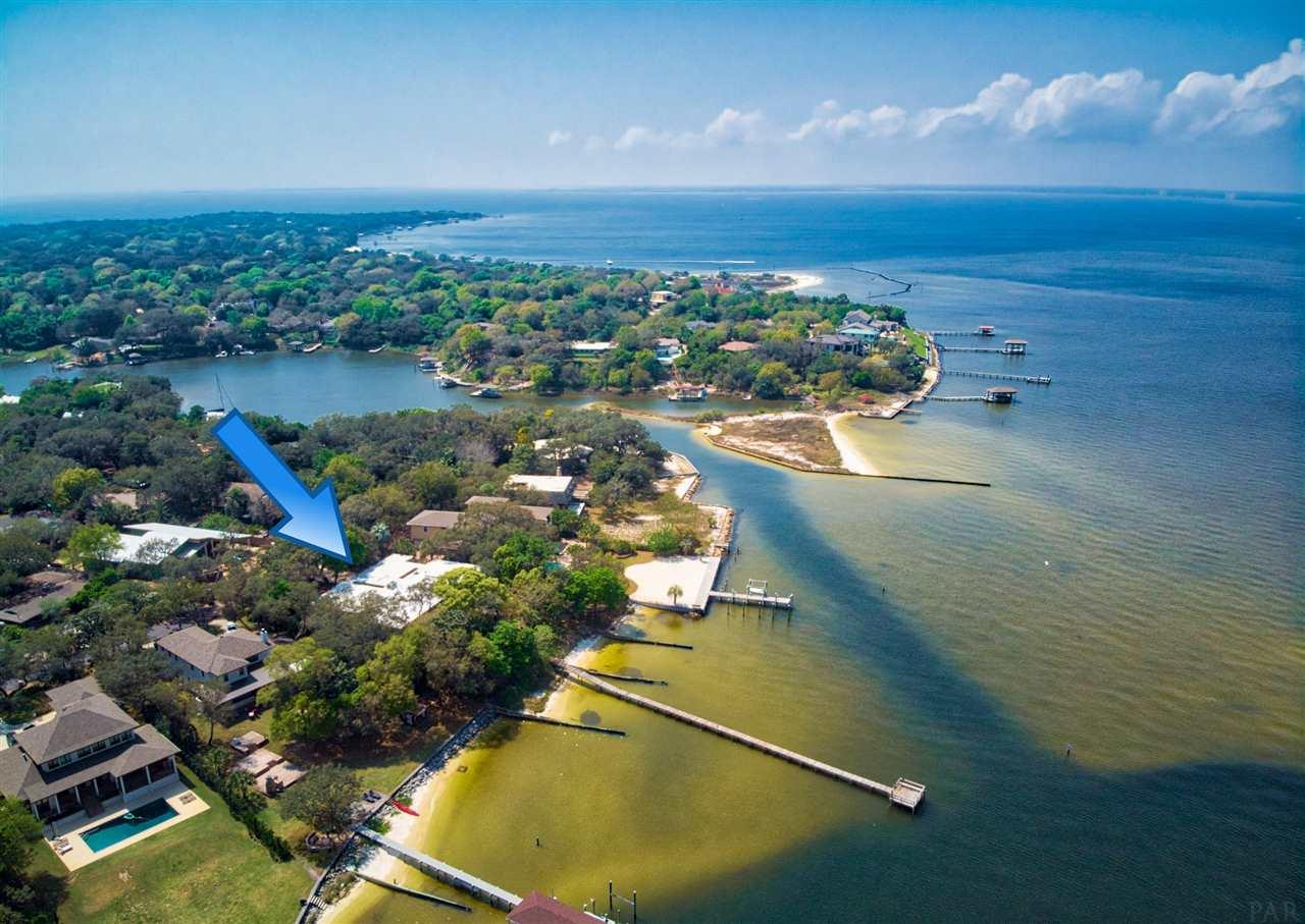 This mid-century modern home was constructed in 1958 on a waterfront home site overlooking scenic Pensacola Bay.  It is near the mouth of Hoffman Bayou in the city of Gulf Breeze, and has been owned by the same family for over 50 years! The property will afford the new owner a waterfront lifestyle that few will ever experience! The combination of high elevation, 175' along the water, a private sandy beach, and deep water are hard to find. The one level home includes over 5200 square feet under roof, with 4741 square feet that are heated and cooled. The floor plan offers a galley style kitchen with abundant cabinetry and adjacent laundry room. The living spaces include formal dining and living rooms, as well as a cozy family room with fireplace.  The waterside master suite offers a bath with garden tub and shower, and a private entrance to a side yard patio with slate flooring.  A large, integral guest suite includes a spacious bath with double sinks, garden tub, and walk-in shower. With three additional bedrooms and a third bath, even a large family could be comfortably accommodated. Other features of the interior are 9' ceilings, terrazzo flooring, and numerous windows offering abundant natural light and exceptional scenery. Once outside, you will find a workshop, storage room with toilet and utility sink, shower, and a two-car carport with paver walkways around the sides. A private pier extends out into very deep water, home to many species of saltwater fish. The yard is filled with oaks, palms, azaleas, rose bushes, and fruit trees, including grapefruit, orange, kumquat, mulberry, and fig. The highlight of the outdoor living space is the expansive waterside patio, which would be a wonderful place for family cook outs or social events. This location is just minutes away from top rated schools, world class beaches, shopping, dining and historic downtown Pensacola.