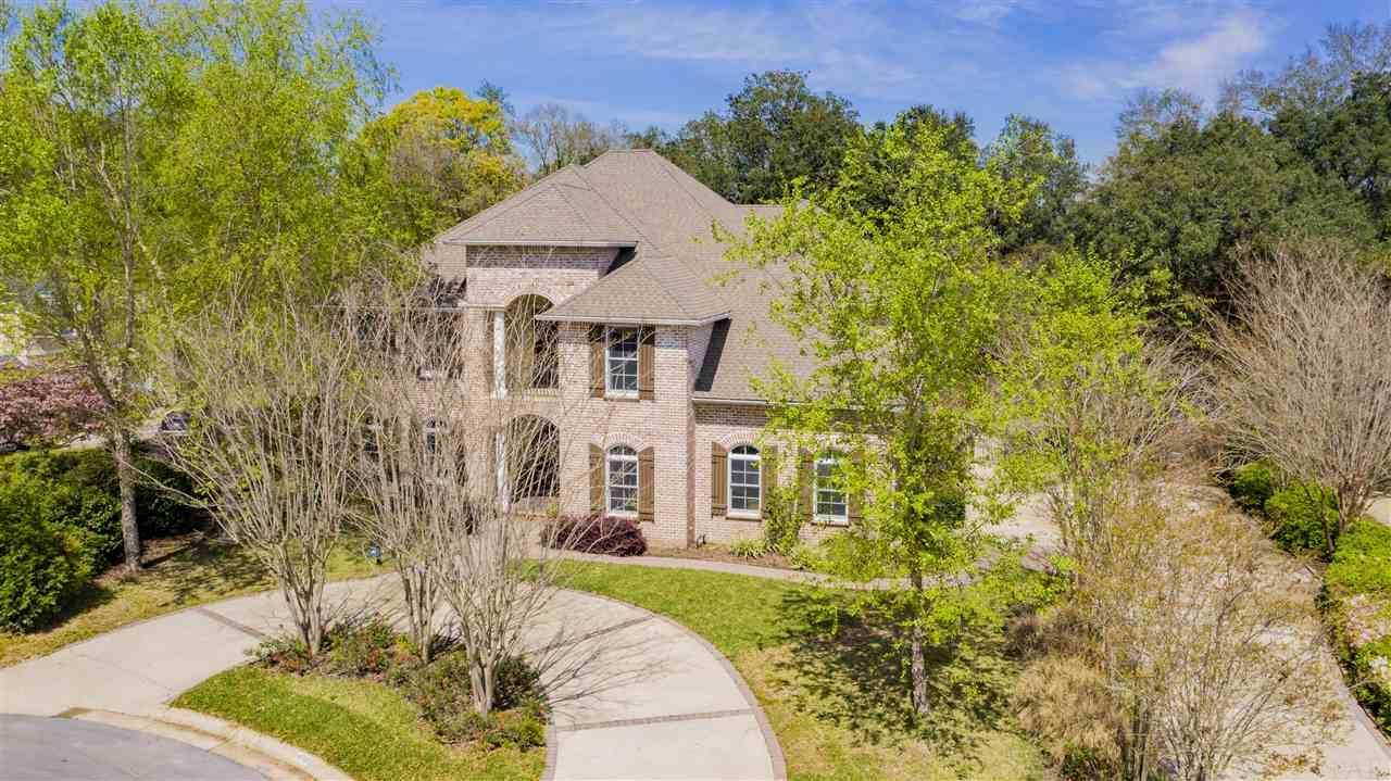 This custom-built luxury home is conveniently located in Bohemia, an established desirable neighborhood located off Scenic Hwy. Driving in, you'll enjoy the mossy Oak trees, up to the quiet Cul-de-sac. Upon entering, note the grand entryway with regal columns and towering 23 foot ceilings. The gorgeous custom hardwood flooring flows through the main living area of the home and into the office. This home offers great entertaining space with a formal dining room, sitting area and sliding glass doors that offer wonderful views of the pool with fountain. Opening up to the covered lanai and saltwater gunite pool, you can enjoy a relaxing evening in your private back yard near the fire pit or grilling out on your built-in outdoor grilling area. There is also a room with en-suite bathroom on the main floor that would make a great in-Law suite with direct access to the outdoor living space. The spacious kitchen comes equipped with ample storage, granite counter tops, kitchen island, large walk-in pantry, recessed lighting, brand new wall oven and built-in microwave. It opens to the breakfast nook and family room with a gas fireplace. Upstairs, you'll find a grand master suite with his and hers walk-in closets, spacious master bath with a 10 head walk-in shower, separate vanities, granite counter tops, garden tub, dressing area and water closet. The master bedroom offers a cozy sitting area that opens to a private balcony overlooking the pool. Three additional bedrooms are located upstairs across from the master as well as 2 full bathrooms and 2 balconies perfect for relaxing. Other notables are a whole house generator, custom baby gate installed around the pool, pool bathroom, custom curtains, alarm system and circular driveway providing additional parking. Don't miss your chance at this luxury home! Check out our full video tour on the MLS and YouTube.