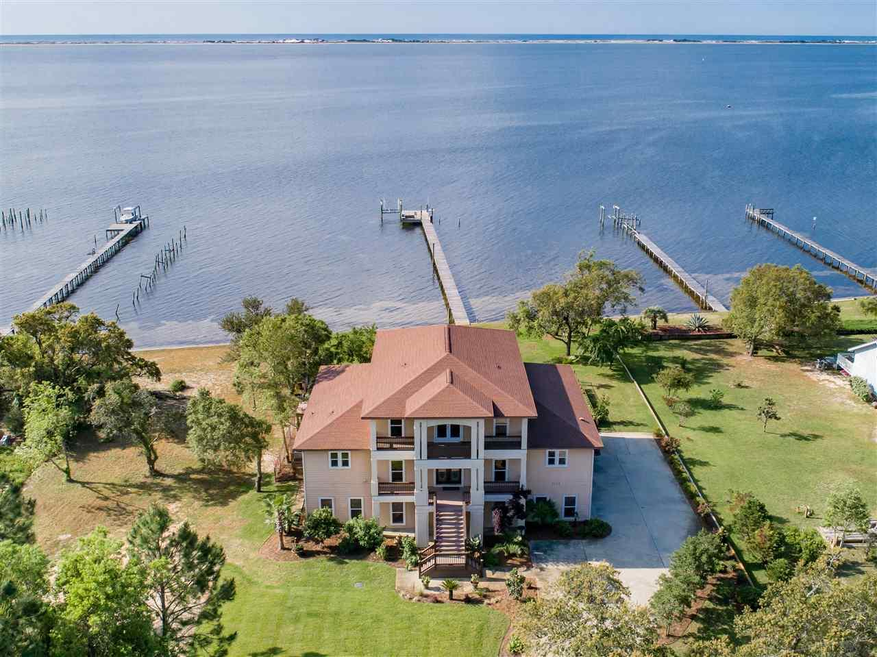 From the impressive exterior of this waterfront manor, the exemplary construction and attention to detail is evident. The well planned, expansive open space, 10' ceilings, 6' impact glass windows and 8' doors with transoms provide generous natural light and dramatic, unobstructed views of the Intracoastal waterway. A deep porch overlooks the resort style gunite pool, dock and water. Inside, woven bamboo floors are gorgeous and complement the wall of custom cabinetry housing the surround sound audio/visual system. An eye-catching two sided gas fireplace is a focal point for both living and dining area. The large dining space opens to the huge chef's kitchen with Italian travertine tile and granite counters is the heart of this home. Unbelievable storage, deep drawers for dishes/pots, tall cabinetry, a coffee nook, ice maker, wine/beverage cooler, corner cabinet with pre wired outlets, and two sinks are highlighted by an immense black granite island providing prep space, storage and seating. Upscale appliances include a 6 burner Dacor gas stove top, Bosch dishwasher, pot filler, KitchenAid refrigerator, built in oven and warming drawer. The large pantry/office has extensive  storage, a refrigerator and a built-in desk. The master bedroom has an amazing water view, sitting area, and an oversized master bath with Italian travertine, granite counters, a walk-in shower with bench and jacuzzi tub. Also, a huge walk-in closet accesses the oversized laundry room. Upstairs, note the 3 sizable bedrooms with large closets and the 2 full baths. Two bedrooms overlook a 2nd large porch viewing south. Ground level features a 3 car garage and cooled bonus room with full bath/kitchenette. It's entertainment ready and just steps from the pool area as well as the new 2018 dock that features lifts for a 10,000 lb boat and a jet ski and green lights for night time fishing. Elevator ready, this space is currently two large closets.! This fabulous custom coastal home is ready for you!!