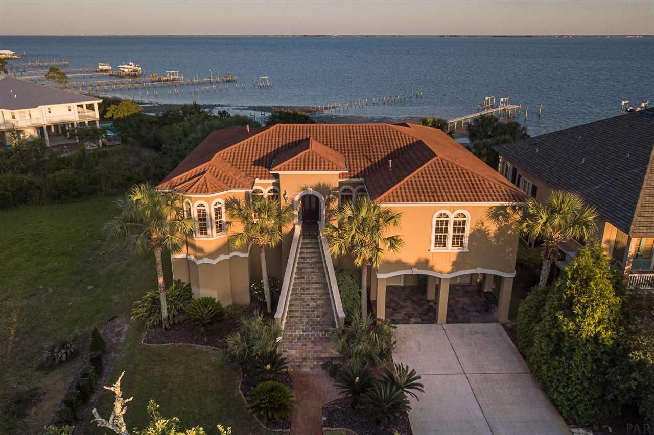 """Mediterranean inspired waterfront residence on Santa Rosa Sound. Over 9000 square feet on two levels, including living areas, decks, outdoor entertainment areas (under roof), garage area, mud room and storage. State of the art ThruFlow maintenance free lighted pier & dock with a boat lift and jet ski port for optimal boating and water recreation. Sparkling saltwater sound front pool with a waterfall, fountain, perimeter multi-color light feature and mosaic tile inlay. Custom built in 2007 with the finest materials and design features with 12' ceiling heights throughout and 8' interior and exterior doors. 2' x 6' exterior wall construction, metal lathe concrete stucco exterior and composite terracotta roof for energy efficiency and wind rating. Sumptuous inside and out, front to back, top to bottom. Stunning front entry with slate tile tapered steps. Interior design features include hardwood and slate tile flooring, premium moldings, 3 cm granite counter tops in the kitchen and all bathrooms, three coffered ceilings, wooden columns, iron railings, 4"""" Plantation Shutters. Ambient designer lighting and a warm palate of rich paint colors, wall coverings and wood grains combine for an elegant and sophisticated, yet comfortable and relaxed waterfront lifestyle. Open floor plan overlooking Santa Rosa Sound and Pensacola Beach with panoramic vistas. Beautifully designed kitchen; custom mahogany cabinets, with Island, Miele 5-burner gas cook top & Miele hood, Viking wall oven, warming drawer and microwave, dishwasher, and a trash computer. Full size elevator. Upper and lower outdoor living spaces for cooking, entertaining and television viewing. Screened, covered upper entertainment area with a built-in kitchen, plus an expansive open deck. Underneath is a covered lanai with hot tub, television and cabinetry."""