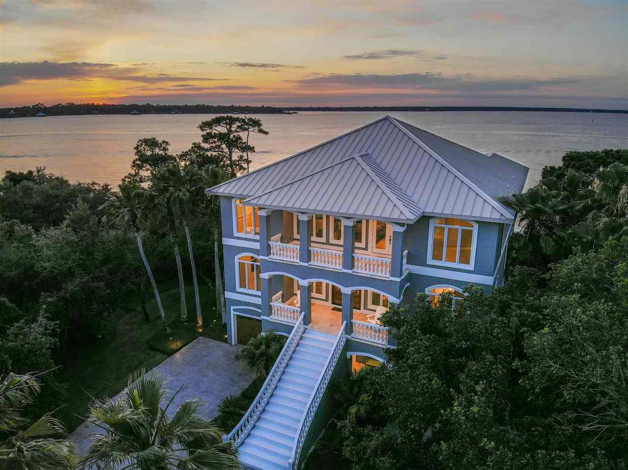 Home of distinction and luxury with the most phenomenal expansive views of Bayou St. John – This newly remodeled 6000+ square foot 5-bedroom 5.5-bath home the exclusive, upscale coastal neighborhood of Ono Harbour offers everything one would want on Ono Island with unbelievable upgrades far beyond what one would expect. Loper Construction built & then refurbished this exquisite home over the last year & the timeless elegance & beauty is truly unmatched. The entry that guides you into the beautifully designed, newly painted residence has been completely redesigned & leads directly into the second floor of the three-story home where you'll enter into an open floor plan with new tile floors throughout, new paint, high-stretching new custom wood ceilings, a custom staircase & retractable chandelier. Main level is ideal for entertaining or simply enjoying island time & features a magnificent great room, new fireplace, & spacious dining room. A chef's kitchen awaits you with freshly painted cabinets, new counter tops, new gas stove, new dishwasher, new refrigerator, new ice maker, & stainless-steel appliances. Watch movies in your own private theatre room with custom Hunter Douglas shades, new air conditioner, new ice maker, & full wet bar for the ultimate cinema experience. Escape to your private master suite on the third floor with a gorgeous new fireplace & updated master bathroom with a soaking tub & separate tiled shower. Additional spacious bedrooms are also on the third floor along with a grand office complete with new ice maker, wine cooler & bar. A guest suite with living space & kitchen on the first-floor lead directly out to the glistening water. Plenty of storage with two climate-controlled rooms in garage. The second parcel across the street on Ono Harbour provides the total package with two lifts–a 16-18000lb. boat lift & second lift for your jet skis. Come take a look and start living the Ono lifestyle – a relaxing coastal island community unlike any other.
