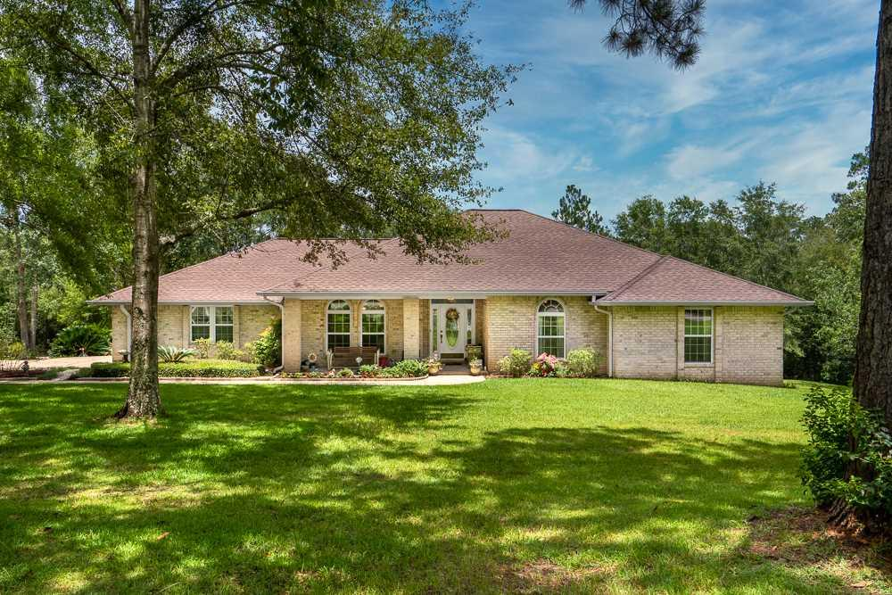 Country Living at its finest! Looking to get away from it all, but would still like to be close enough to enjoy everything? This private home on an estate-sized lot is just what you're looking for! Only 13 miles from I-10 access, and less than 25 miles from Downtown Pensacola. Loaded with extras, this spacious custom-built all brick home sits on over 6 acres, and features a screened-in pool, a beautiful pond with it's own fountain and sitting areas, a fenced garden area, and a secluded camping lodge for outdoor adventures on your private estate! The wooded areas of this property have custom made trails for relaxing strolls along the creek, or golf cart rides. This great home offers 1-level living with 3 foot doorways and 4 foot hallways thr