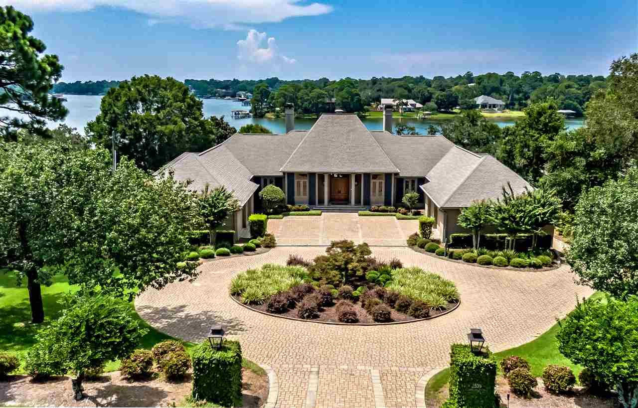 The original owner selected this site for its' strategic location that provides some of the most sweeping water views on Bayou Texar, its high elevation and, large 3/4 acres with 150' of water frontage. It's one of the most valued locations on the Bayou and central to everything in Pensacola. The French Provincial style is timeless and the home was carefully constructed to last for generations by using outstanding craftsmanship and high-end materials. The floor plan was very carefully thought out and is still very much in keeping with the newer homes of today. The home was designed to take full advantage of the amazing water views with numerous large windows and outdoor living with two 9' x 34' covered areas on each level overlooking the backyard. The first level verandah is accessible thru 3 sets of mahogany doors in the living room to enjoy the prevailing summer breezes and spectacular sunsets. The lower level has an outdoor natural gas grill. All the rooms are spacious with high ceilings (14' in living room and 10', downstairs 9'ceilings.) A study and the expansive master suite encompass the entire south end of the first level - both with water views. The other two bedrooms (each with its own full bath) are located downstair on either side of the large family/media room. There is also a large 729 sf workshop on this level with a garage door access - possible 4th bedroom. There's nothing like living on protected waters, especially when you have direct access to the Gulf waters with world class fishing. The two 2 covered boat lifts are equipped with electrical and water, storm resistant Thruflow decking (2018), plus a wave runner lift, and uncovered boat slip for guest. The 60' gunite, salt water lap pool has a deep end section and ample deck area for relaxing. After a swim you can head to the gym/spa on the lower level which is accessible to the backyard and features a full bath, dry sauna and steam shower. This home is what Florida living is all about.