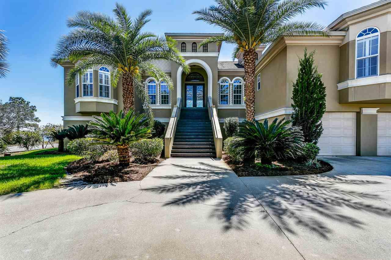 Don't miss this truly captivating waterfront 4/4.5 home!!!  Enjoy the views of the Emerald Coast Santa Rosa sound in this elegant, custom designed home that was featured by H&G Magazine.  Indulge in the luxury of a home theater which could also be used as a fourth bedroom, a wine closet with distinctly crafted iron/copper doors, a well appointed wet bar and a grand master bedroom with panoramic water views with 10 ft tray ceilings. The grand master bath promotes a serene sanctuary. Newly installed bamboo flooring in all bedrooms, closets and office area.  The generously sized kitchen offers GE Monogram appliances and flows between the dining room and two living areas. Equipped with manicured landscaping, a 1,200 sq ft lanai and a pier with dual boat lifts. Nestled in Smugglers Cove in the quiet part of Gulf Breeze, this neighborhood offers a number of amenities that include a clubhouse, lap pool, and tennis courts. A truly distinct home fit for royalty!  Call and make an appointment today!!