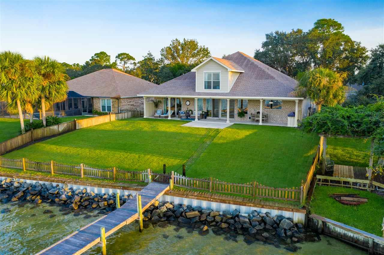 """Welcome home to waterfront leaving at its best .....Simply Stunning Custom-Built home nestled on one of the most picturesque locations in East Navarre offering a private 240 ft. dock, 6,000 Lb. boat lift, and seawall overlooking the Santa Rosa Sound and Navarre Beach! Enjoy breathtaking sunrises and sunsets daily on your 52 ft back porch....perfect for spending time outside with a soft coastal breeze and your Summer kitchen to make the most of the wonderful Florida evenings to cook out and entertain. Home is only 5 years young exquisite inside and out. On entering the home you will immediately appreciate the attention to detail and the coastal living theme with high ceilings ~crown molding, wood plank tile flooring all enhanced by the soft color palette of grey and white for a light fresh and bright feel in every room.    A wall of windows across the entire living area brings the outside in with amazing panoramic views of the water and Santa Rosa Island ~Living room features built in bookcases on either side of the Natural gas focal point fireplace, Surround sound with 5 built in speakers ,recessed lighting and floor outlets~ open flow to the dining area with decorative columns and detail knee walls set the stage for a great entertaining area or formal dining.  Gorgeous Gourmet custom designed kitchen is framed by a beautiful brick archway ~ ceiling height solid wood shaker cabinetry with soft close doors and drawers, pull out shelves, lift platform for a blender, center island has a prep sink & drop down seating area with banquette bench & storage~ 48 """" Jennair Gas cooktop with griddle and grill .Decorative mantel hood with pull out spice racks ~built in oven and microwave ,elevated dishwasher and large single under-mount porcelain sink ~ Huge walk in pantry with shelving and 16"""" bottom shelf with electric receptacles for your favorite appliances. Heart of the home in the kitchen is enhanced by the picture swept head window for wonderful water views."""
