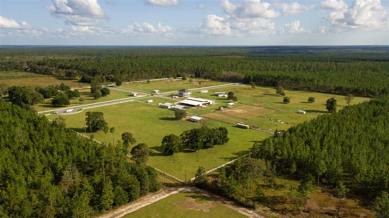 HUGE PRICE REDUCTION ON This Exquisite Equestrian Property in the heart of the Blackwater River State Forest.  Tucked away behind a gated entrance in the center of 40 Beautiful acres is a Custom 2900 SF, two story home with granite countertops, crown molding, 10-foot ceilings and covered porches that allow park views for miles.  The Custom 20-Stall Barn with Priefert Stall Fronts and several tack/feed rooms as well as 2 bunk houses for your Ranch hand or trainer, a 300' X 175'  lighted arena, and acres of fenced pasture, will meet all your equestrian needs. In a community that attracts horse enthusiast from all over, the Blackwater Equestrian Center can offer a variety of income producing options from renting stalls, to campsites to selling or leasing ten 1.3 acre parcels already platted with the County.  All this  ideally located in the heart of the forest that offers trail riding, canoeing, kayaking, fishing, hiking, camping and hunting, and just a 60 minute drive to the Beautiful Beaches on the Gulf of Mexico.