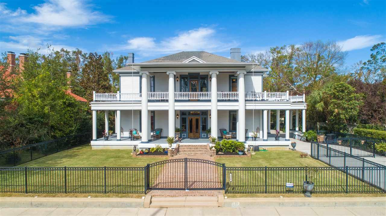 Constructed in 1908 by the Sublett Family, this exquisite Neo-Classical Estate has been fully restored to it's original grandeur with no detail spared. After falling into disrepair and purchased by it's second homeowners in 2004, 4 full bathrooms and a powder room were added as well as a fully renovated kitchen. All porches were reconstructed as well as all new plumbing and wiring installed. This home is perfect for entertaining with a parlor with wet bar, living room, formal dining room with butlers pantry with wet bar and ample outdoor living space on two levels that encompass the home. You'll note the incredible craftsmanship, fully restored wood detail and beautiful hardwood floors and pocket doors as well as 9 fireplaces with original tile work and elegant chandeliers throughout the home including an original stained glass window in the dining room. The kitchen is equipped with custom wood cabinetry with pull-out drawers a 5 burner gas cooktop, double wall oven, wet bar, ice maker, trash compactor, 2 drawer dishwasher, pantry and ample cabinet storage. The sizable master suite has his-and-hers walk-in closets, jetted tub with a separate walk-in shower, water closet with an additional vanity and 2 gorgeous detailed fireplaces. Other notables are fully fenced lot and back alley entry with ample parking with carport, built-in grill and outdoor cook space and a wonderful sun deck on the second floor and original glass windows. You'll enjoy the stately charm of North Hill and the existing trolley tracks that meander right down Desoto St. as well as neighborhood parks and sidewalks. Located less than a mile to downtown Pensacola where you can enjoy a plethora of restaurants, shopping and entertainment. Check out our full video tour on the MLS and YouTube.
