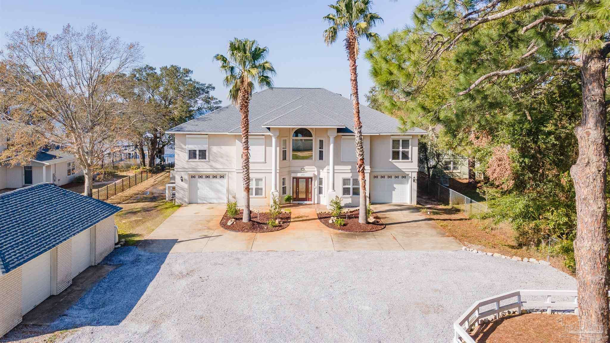 This home has it all! Gulf breeze Bayfront custom home was built in 2006 by Russell Builders. This charming coastal retreat is located on the boater friendly East Bay. Home offers lovely sunsets with a northwestern exposure. Enjoy fishing from your 50ft pier equipped with a wave runner lift. This lot is very private and deep (320ft) with a private entrance.  Quality construction with  concrete reinforced with rebar block downstairs and upstairs with 2x6 exterior frame with durarock and hard coat stucco for exterior. The interior boast an elevator, intercom & radio throughout home and patio. Two kitchens (one downstairs with hobby room), separate living downstairs with separate kitchen and entrances. Main kitchen level has gas cooking, separate office, crown molding, great room, with 2 French doors and lots of windows, granite in the kitchen stainless steel appliances, oven warming drawer, dual drawer dishwasher, an ice maker, and plenty of cabinets & built ins. The split floor plan includes bedrooms up and downstairs with a potential for five bedrooms ultimately. The master bedroom has a gas fireplace with a cozy waterfront seating area and also a large master bath and walk in closet. The home boasts an abundance of balcony space from the main living area and master suite. The 1st level has an additional covered porch with 3 french doors. The floor plan affords water views from most living areas. The oversized master suite is on the upper level to maximize the best water views. Existing playhouse on the grounds with water and electric access. Plenty of parking and uses for all the space. Two car garage plus a workshop and detached two car garage for additional parking or storage.  Really multi use with the space and buildings as this owner had her hobby room for grooming dogs and the set up is still in place with ample uses. Close to beaches and Navarre and Gulf Breeze.  Newer one owner home with so many possibilities for the family and extended family.