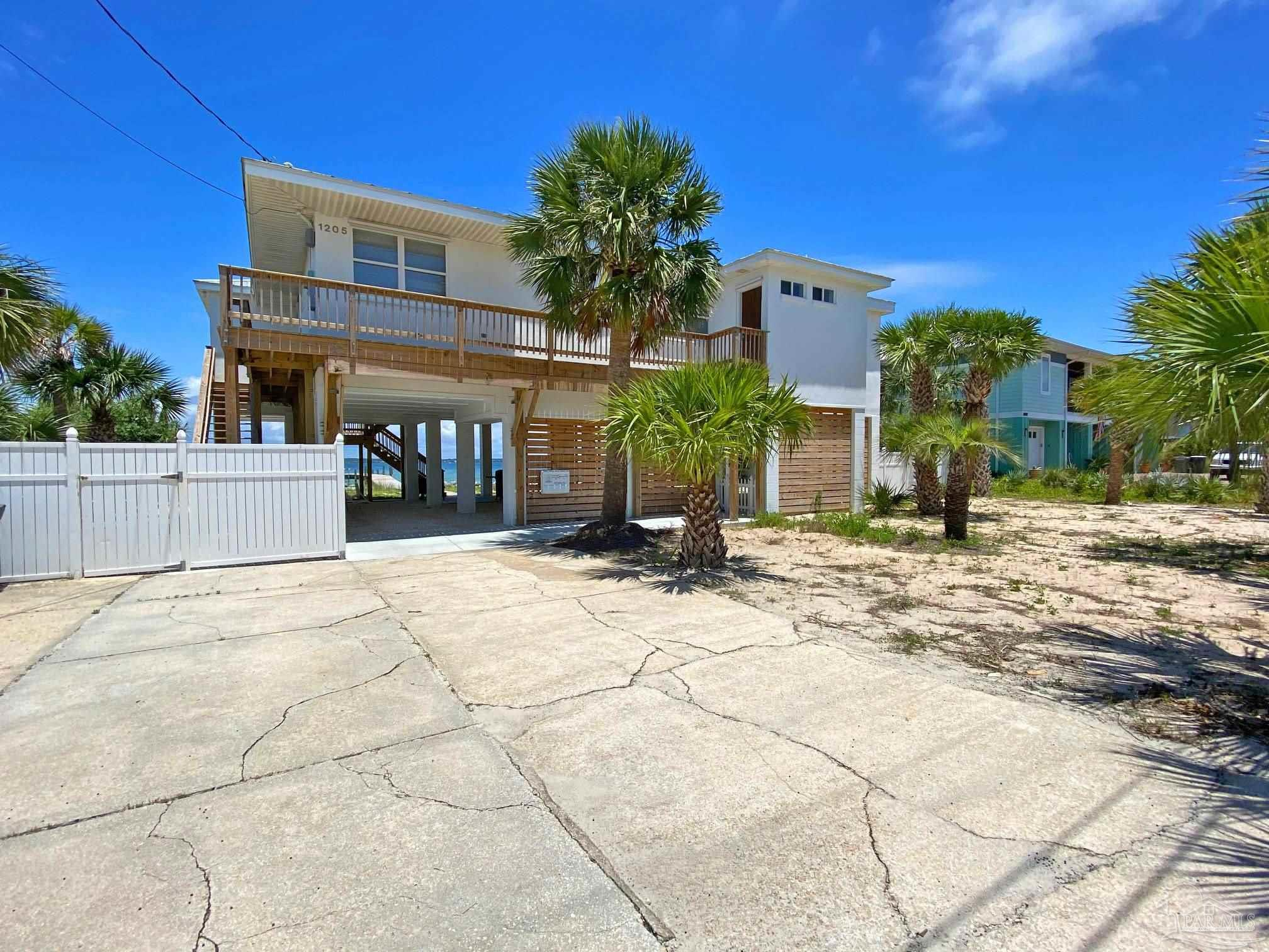 Located directly on Santa Rosa Sound, this home (elevated off ground in June 2019) offers outstanding views of beautiful Santa Rosa Sound. This home was an original cinder block cottage that was elevated to make is less susceptible to rising water. Because the structure is elevated with no ground floor living the flood insurance is now very reasonable.   This home offers 5 bedrooms and 3 baths and with current configuration is set up to sleep a maximum of 16. Most of the home has the original terrazzo flooring. The new master bedroom and master bath which were added in 2020 have porcelain tile.   The kitchen is large with abundant work space and a nice size pantry. The north facing wall of the kitchen has multiple windows offering a panoramic view of Santa Rosa Sound. There is a door onto the large covered deck from the kitchen as well as 2 sets of French doors from the living/dining area onto the deck.   The area under the home is ideally setup for outdoor living. The yard is fenced if you have family members of the 4 legged variety. There are steps into the water on the west side of the lot and a pier for your boating and fishing enjoyment.   This is a great Florida beach house if you're looking for a place to relax and enjoy the beauty of Pensacola Beach. This is not a water front mansion where you have to worry about someone walking in with sand on their feet. With this home you get the laid back lifestyle and an opportunity to enjoy the beach the way your parents and grandparents did in the 1960's but with modern conveniences.   Home is offered fully furnished so all you need is shorts, swim suits and flip flops to embrace the beach lifestyle.   All measurements to be verified by buyer.
