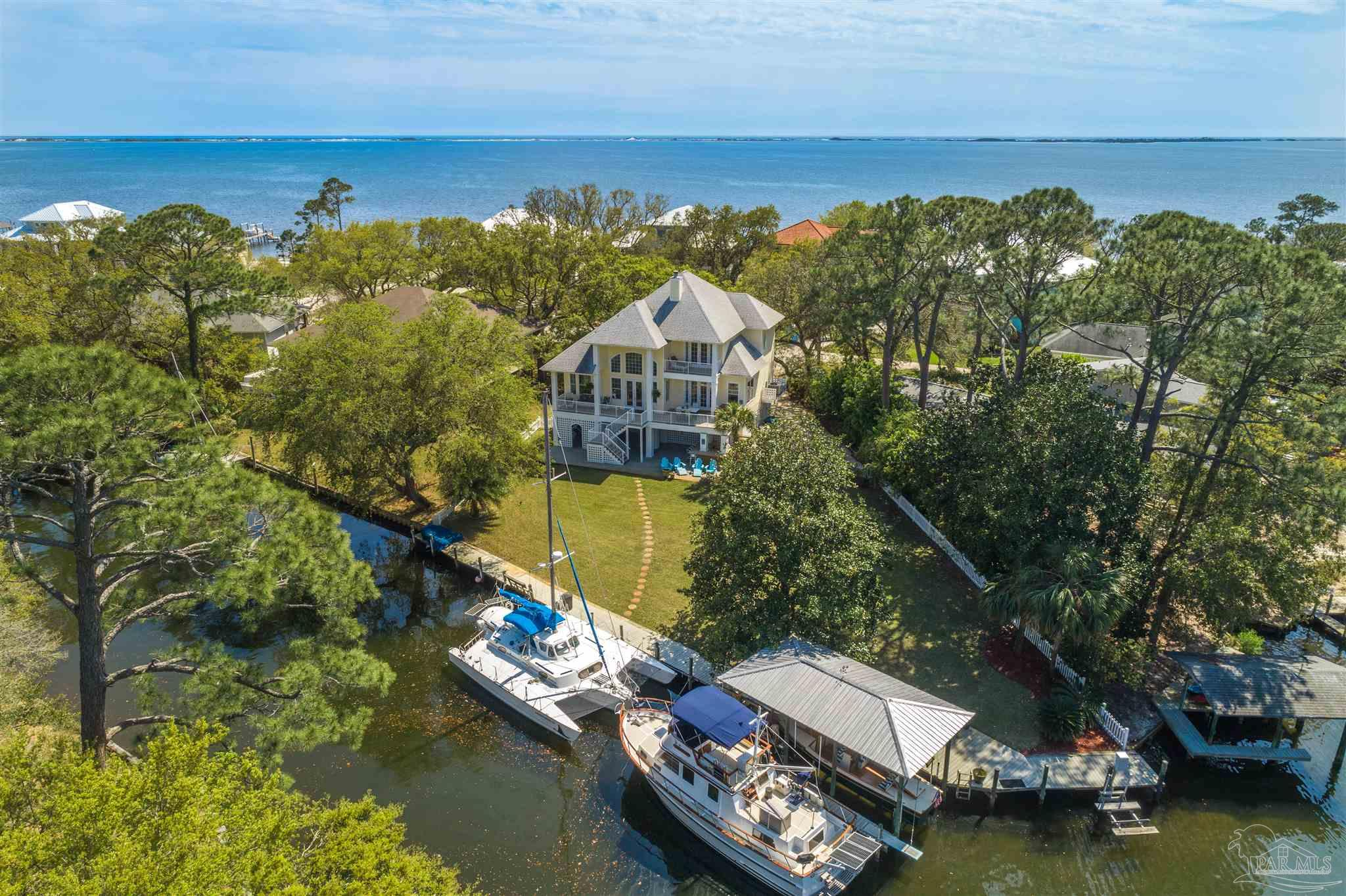 Located on a cul-de-sac just steps from the Santa Rosa Sound with 135 feet of deep water canal frontage, this home is the epitome for Florida living! You'll enjoy the 26 foot, 10,000 pound boat lift with boathouse, jet ski lift, 50 amp to dock and room for 2 additional large boats. This backyard oasis features an outdoor kitchen with built-in grill with mini fridge and microwave, large bar area perfect for entertaining with covered (33x22) and open lanai, outdoor shower, firepit and sizable back yard. The 2 car garage has a large additional workshop space and covered storage area (17x13). Also located on the bottom floor is a brand new addition. You'll find a bedroom with a kitchenette, bathroom with walk-in shower and mini split HVAC. This space would make for a good guest or in-law space or even an airbnb. On the main living floor, you'll find the master suite, kitchen and living space with water views from every window. The kitchen comes equipped with granite counter tops, gas cooktop, breakfast bar and stainless appliances. Just off the kitchen is the dining room and spacious living room with a fireplace and cathedral ceilings. You'll enjoy the ample natural light throughout the home as well as the custom Eastern White Pine hardwood flooring imported from New York. The master suite has French doors with a separate entrance to the covered balcony providing water views and the bathroom has a walk-in shower with 2 shower heads, heat lights, double granite vanity, urinal and a large walk-in closet. The 3rd floor has 2 additional bedrooms and a full bathroom with a shower-tub combo. Other notables are IMPACT GLASS, large balcony with dining and living area on second floor just off the main living area, office nook just off the kitchen, powder room, recessed lighting, surround sound, crown molding, beautiful oak trees, and second bedroom upstairs has a private balcony overlooking the water. Check out our full video tour on the MLS and YouTube.