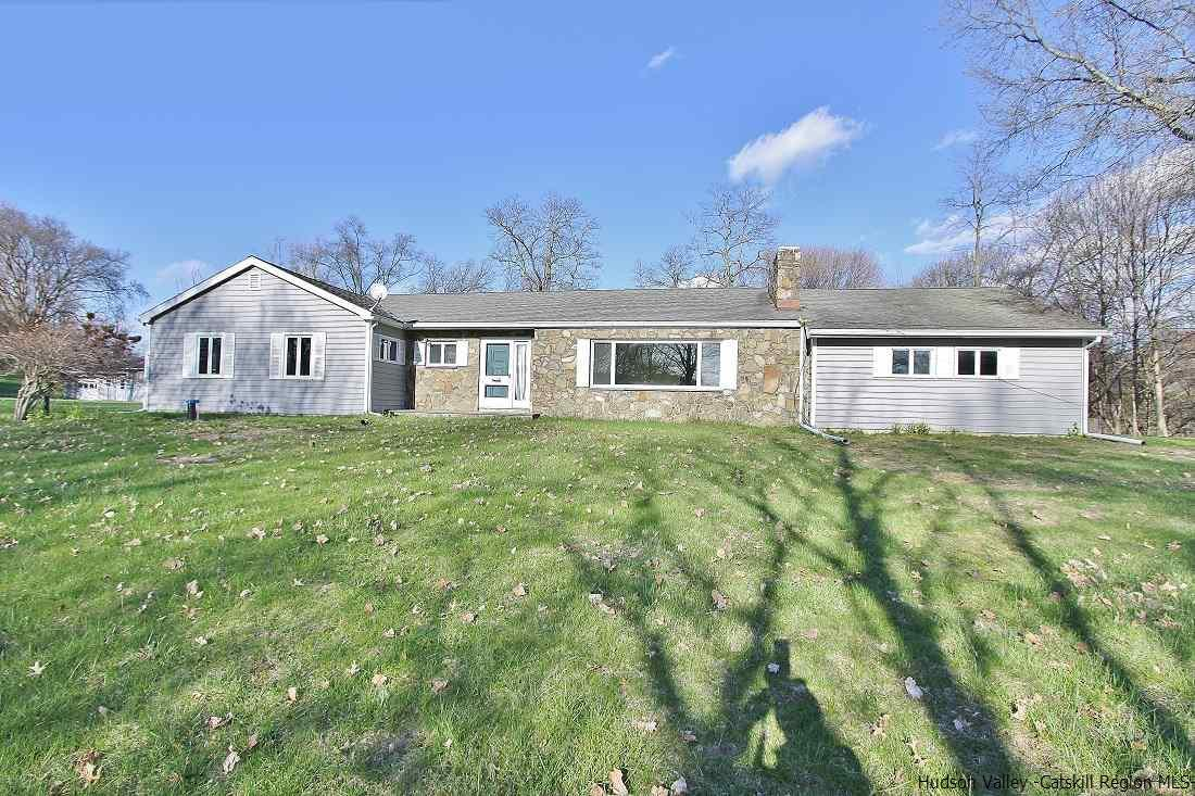 Sprawling brick ranch offering large light-filled rooms, an open kitchen and nicely landscaped grounds. Enjoy 4 bedroom, 2 ½ bath situated on 3 acres. Home is located close to the Village of Rhine beck, Red Hook , NYS Thruway Exit,  shopping, restaurants and more. Living room is enhanced with a stone fireplace and big picture window. The dining room flows into the living room that is perfect for entertaining. Bright and airy kitchen  has all wood cabinets with an island. Carpet floors extend down the hall to all 4 bedrooms with hardwood flooring underneath.  Basement is  unfinished  with access to one car garage. Behind the home is another 3 car detached garage that is also used as a workshop with electric.  Home overall is in good condition just needs cosmetic updating.